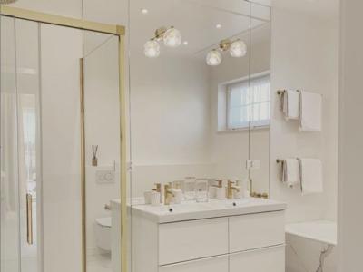 Kryształowa łazienka – złote kinkiety Cruz wkomponowane w lustro